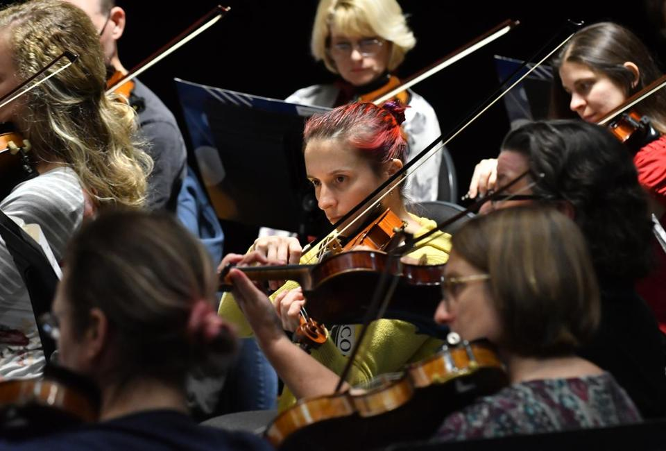 Violinist Johanna Szarkowski (center) focuses as she and her fellow members of the Melrose Symphony Orchestra follow the lead of Music director Yoichi Udagawa.