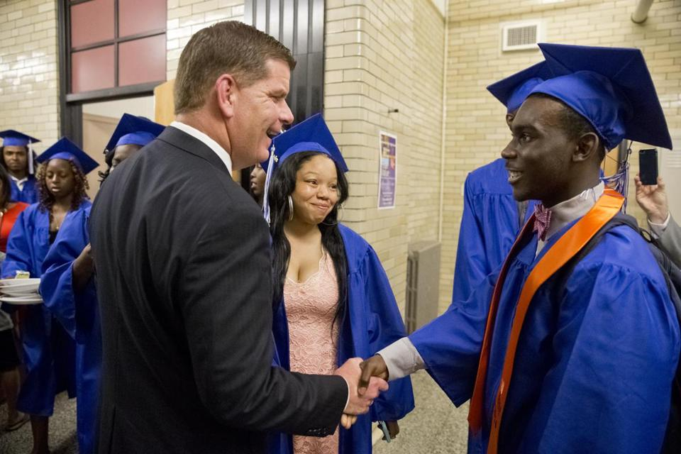 Martin Walsh greeting future graduate Milton Harris a member of the Build Program before his graduation ceremony at Jeremiah Burke High School in June 2016.