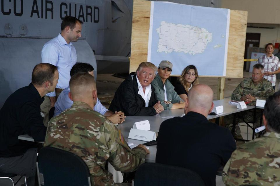 President Donald Trump and first lady Melania Trump participate in a briefing on hurricane recovery efforts with first responders at Luis Muniz Air National Guard Base, Tuesday, Oct. 3, 2017, in San Juan, Puerto Rico. (AP Photo/Evan Vucci)