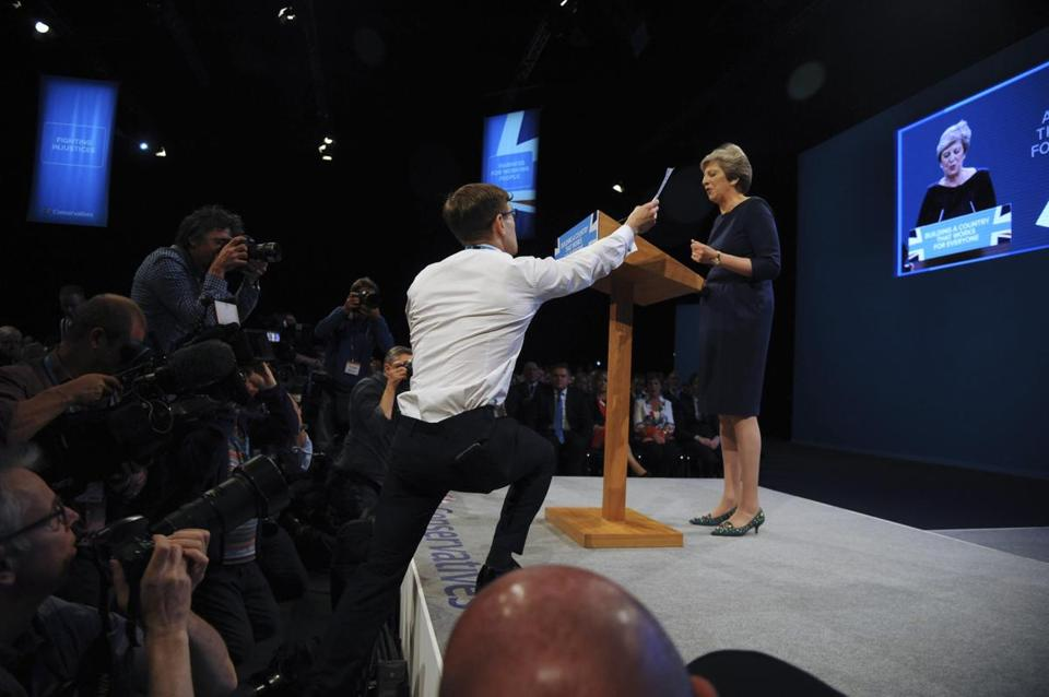 Comedian Simon Brodkin, also known as Lee Nelson, handed UK Conservative Party Leader and Prime Minister Theresa May an unemployment form during a speech.