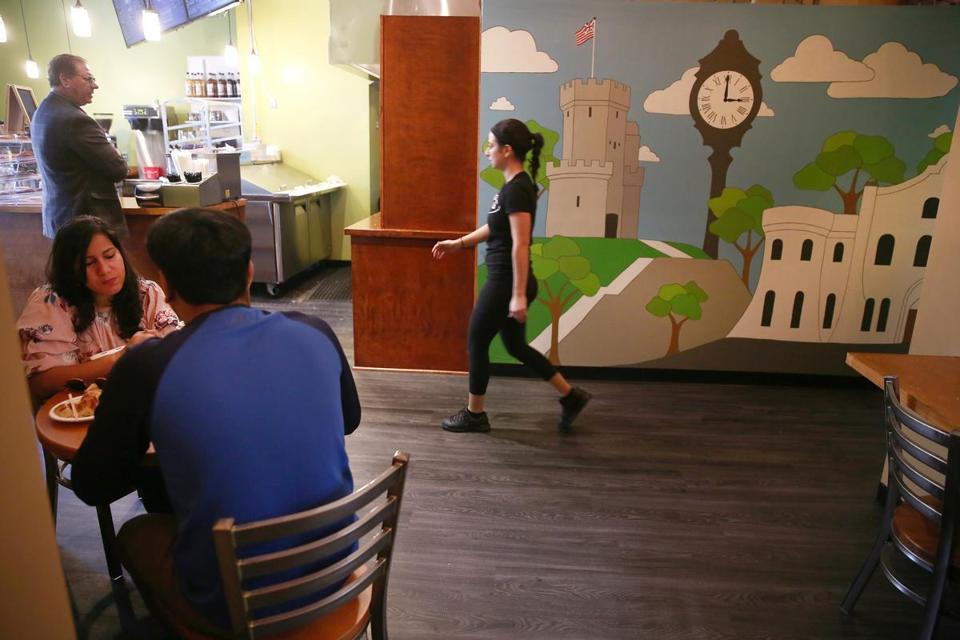 Manager Maria Dardonis walks past a mural featuring Somerville landmarks at Davis Square Donuts & Bagels.