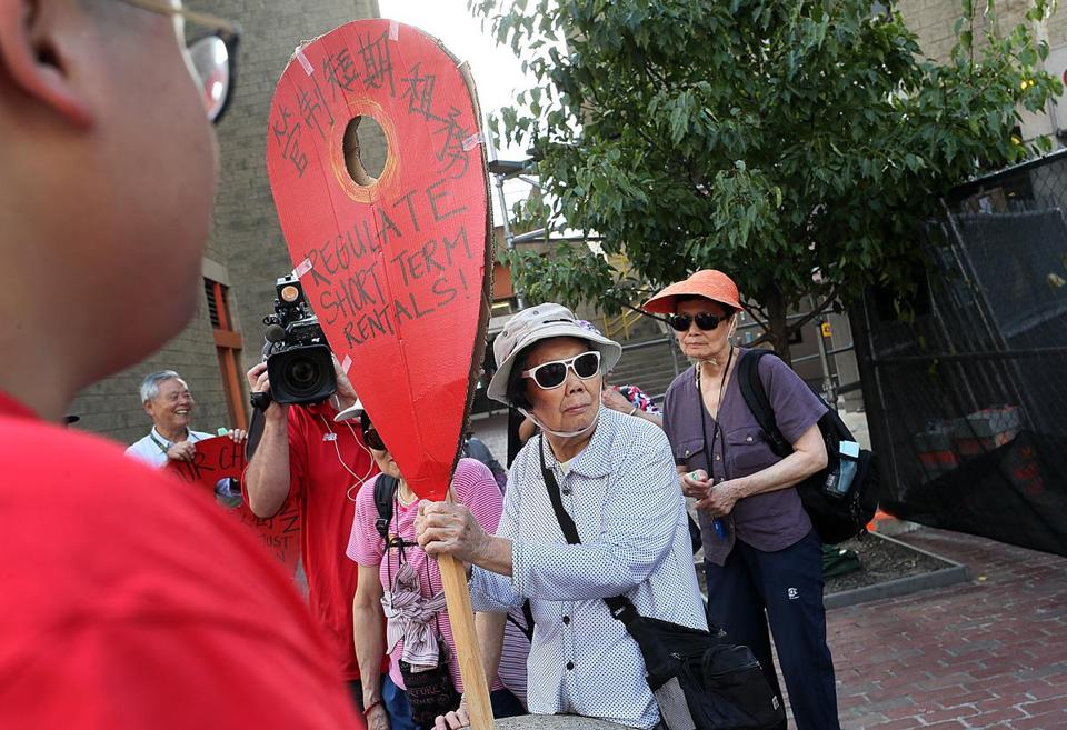 Dierong Lin held a protest sign in Chinatown on Thursday.