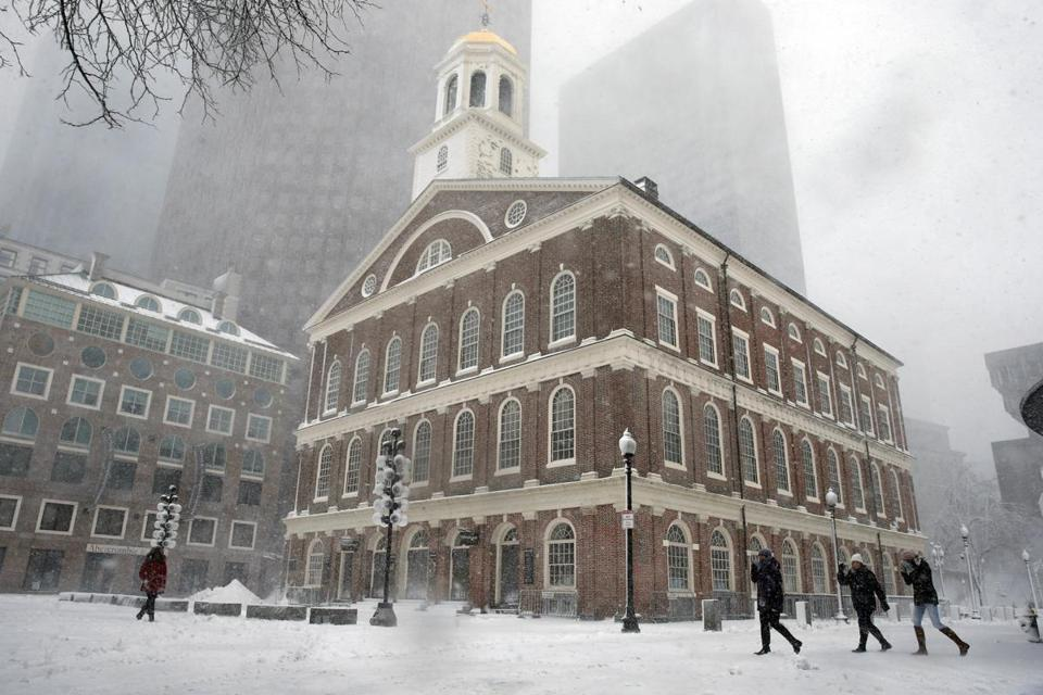 FILE- In this March 14, 2017 file photo, people walk past Boston's Faneuil Hall, which was named after Peter Faneuil, a successful merchant and trader whose ships carried slaves between continents as well as the normal dry goods, spices and wares. The national soul-searching over discriminatory symbols has some cities now scrutinizing whether monuments to contentious figures should be removed. And historians are questioning how to draw the line, cautioning against the fast removal of monuments without thinking through why they're being removed, and the collateral impact the removal may have. (AP Photo/Michael Dwyer, File)
