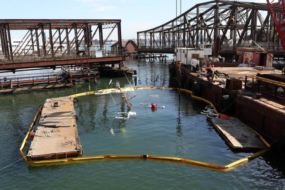 A sunken boat in the Fort Point Channel Boston being worked on to refloat by the use of a crane and divers on Thursday.