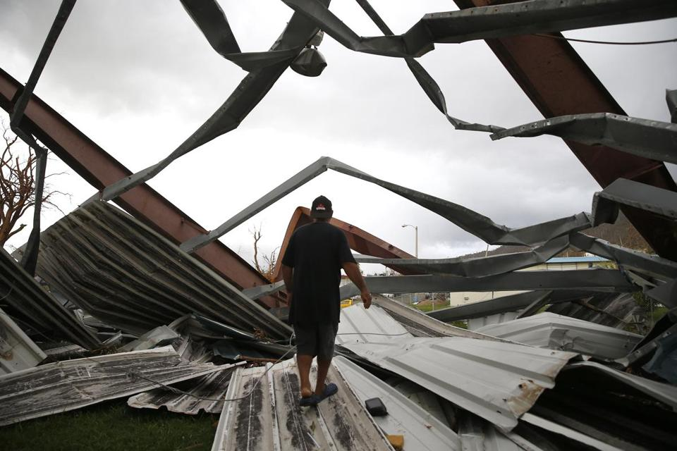 Yabucoa, Puerto Rico -- 9/29/2017 - A neighbor walked out on a piece of metal that fell on Carmen Charriez's home when Hurricane Maria hit. (Jessica Rinaldi/Globe Staff) Topic: Reporter: