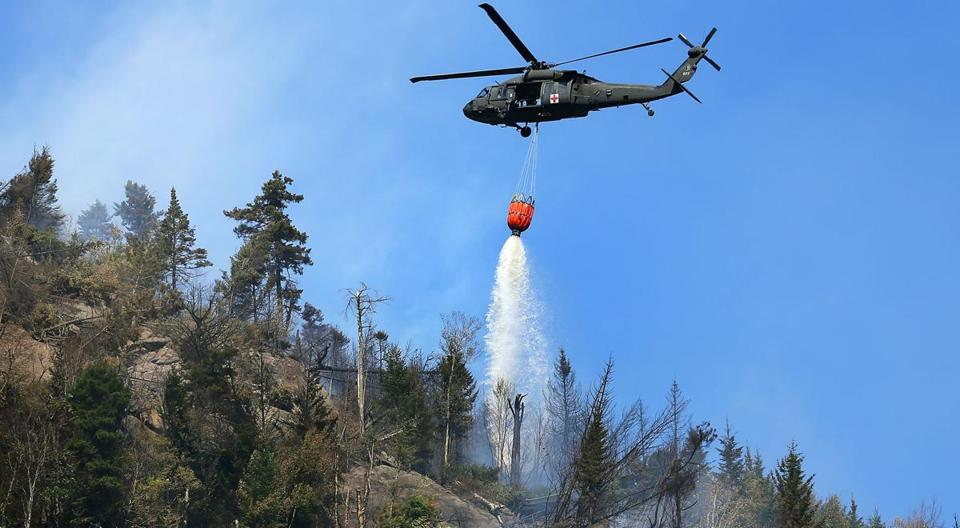 A black hawk helicopter dumped water onto a fire burning in the White Mountains.