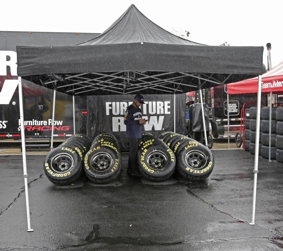 A crew member stands by tires protected from the rain before a scheduled practice for Sunday's NASCAR Cup Series auto race at Charlotte Motor Speedway in Concord, N.C., Saturday, Oct. 7, 2017. Rain has delayed activities at the track. (AP Photo/Chuck Burton)