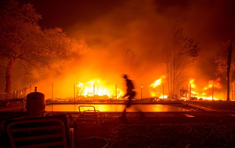 A Firefighter Walked Near Pool As Neighboring Home Burned In The Napa Region Of