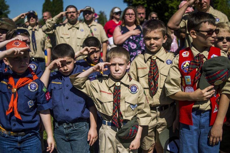 FILE - In this Monday, May 29, 2017 file photo, Boy Scouts and Cub Scouts salute during a Memorial Day ceremony in Linden, Mich. On Wednesday, Oct. 11, 2017, the Boy Scouts of America Board of Directors unanimously approved to welcome girls into its Cub Scout program and to deliver a Scouting program for older girls that will enable them to advance and earn the highest rank of Eagle Scout. (Jake May/The Flint Journal - MLive.com via AP)