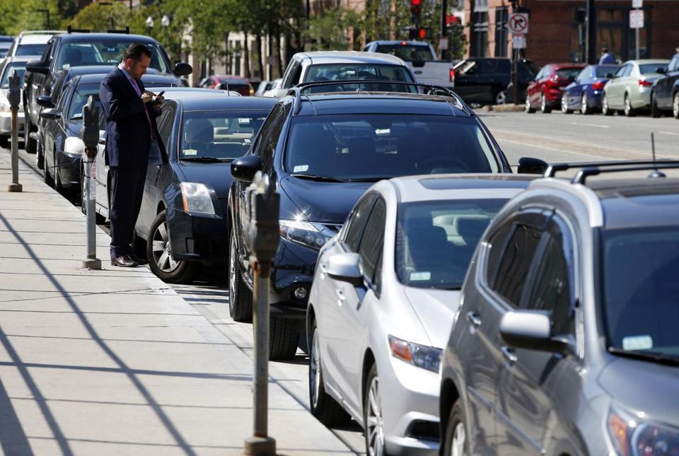 A man checked his phone after parking on Columbus Avenue in Boston.