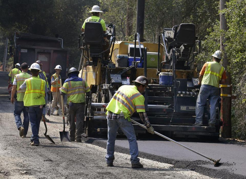 A street paving crew spreads hot asphalt on Friday, Sept. 1, 2017, in Orinda, Calif. Dozens of cooling centers opened throughout California, schools let students out early and outdoor events were cancelled as temperatures soared from a heat wave expected to last through the Labor Day weekend. (AP Photo/Ben Margot)