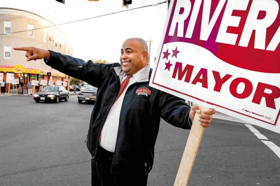 Lawrence Mayor Dan Rivera holding a sign waves at motorists at the corner of Park and Lawrence Streets in Lawrence, MA. Friday, Oct. 13, 2017. Lawrence Mayor Dan Rivera, who has been trying to steer this city's ship straight, faces a fierce challenge in November from William Lantigua, the notorious mayor he ousted four years ago with promises to clean up the city. CREDIT: Cheryl Senter for The Boston Globe