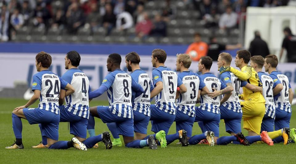 Players of Berlin kneel down prior to the German Bundesliga soccer match between Hertha BSC Berlin and FC Schalke 04 in Berlin, Germany, Saturday, Oct. 14, 2017. (AP Photo/Michael Sohn)