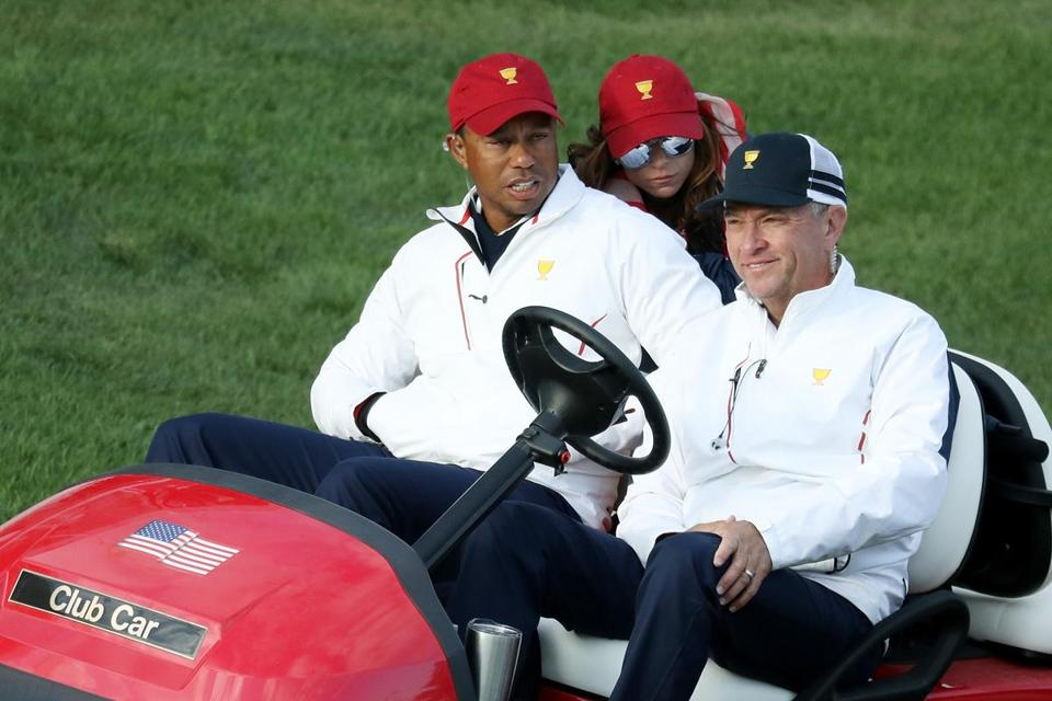 JERSEY CITY, NJ - SEPTEMBER 30: Captain's assistant Tiger Woods of the U.S. Team, Erica Herman and Captain's assistant Davis Love III of the U.S. Team look on during Saturday four-ball matches of the Presidents Cup at Liberty National Golf Club on September 30, 2017 in Jersey City, New Jersey. (Photo by Rob Carr/Getty Images)