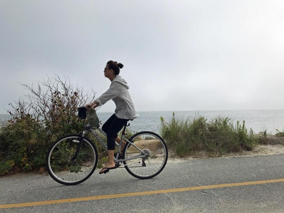 A cyclist on the Shining sea bikeway travels north,passing Surf Drive Beach and vineyard sound.