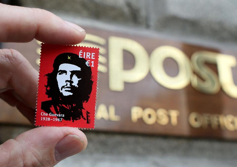 "A stamp, released by Ireland's post office, An Post, featuring an image by Irish artist Jim Fitzpatrick, of Argentine revolutionary leader Ernesto ""Che"" Guevara is held up outside the General Post Office (GPO) in Dublin, Ireland on October 10, 2017. / AFP PHOTO / Paul FAITHPAUL FAITH/AFP/Getty Images"