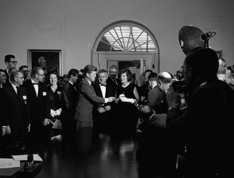 After signing a bill on the care of children with mental disabilities, President Kennedy handed the signing pen to Eunice Kennedy Shriver.