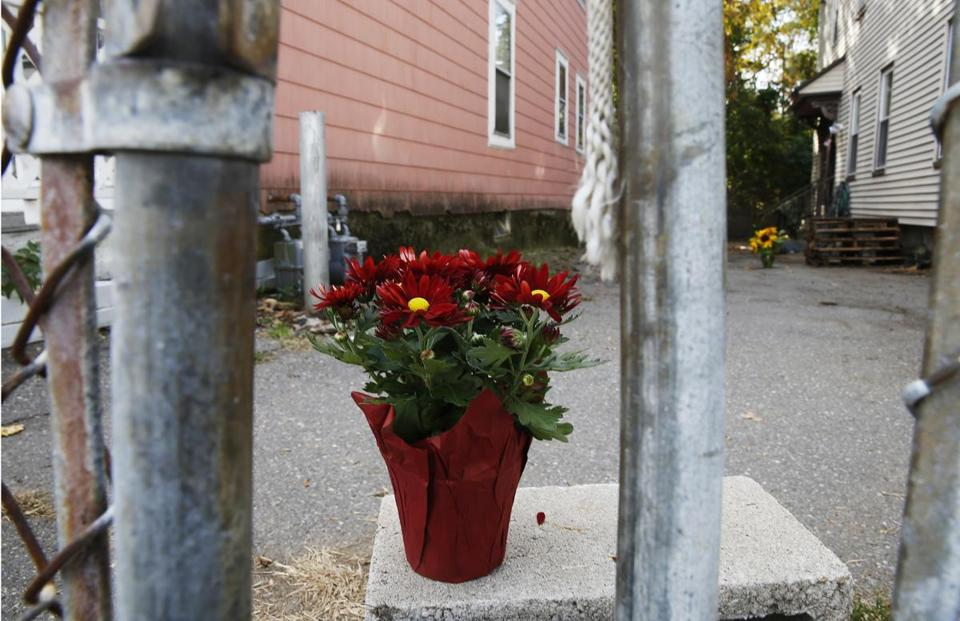 Lowell, MA -- 10/22/2017 - Flowers sit inside the fenced in area where a seven year old boy was killed by two pit bulls is seen in Lowell. (Jessica Rinaldi/Globe Staff) Topic: 23pitbulls1 Reporter: