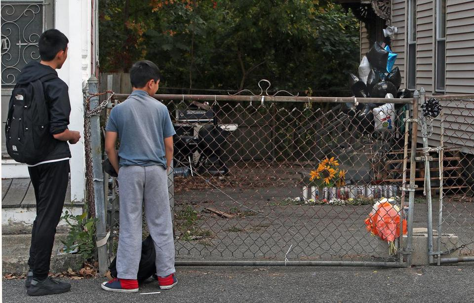 Lowell, MA: 10-22-17: Two neighborhood children pause and check out the memorial at the scene where a 7 year old boy was mauled to death by two pit bull dogs on Saturday on Clare Street. (Jim Davis/Globe Staff)