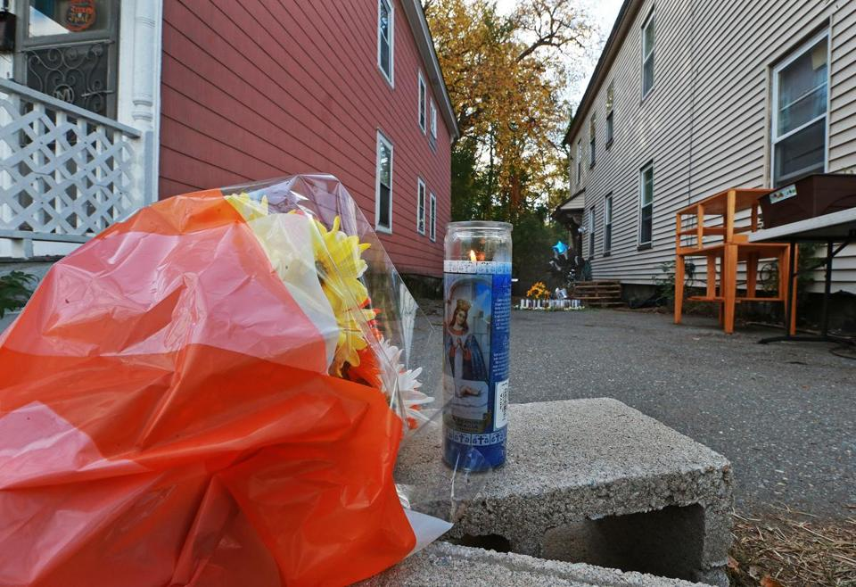 Lowell, MA: 10-23-17: Flowers and candles mark the scene where a 7 year old boy was mauled to death by two pit bull dogs on Saturday on Clare Street. (Jim Davis/Globe Staff)
