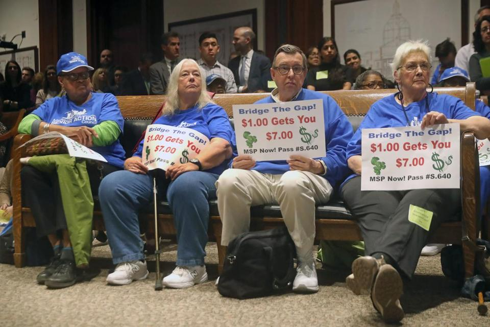Massachusetts Senior Action Council members held signs Monday at a State House health care hearing.
