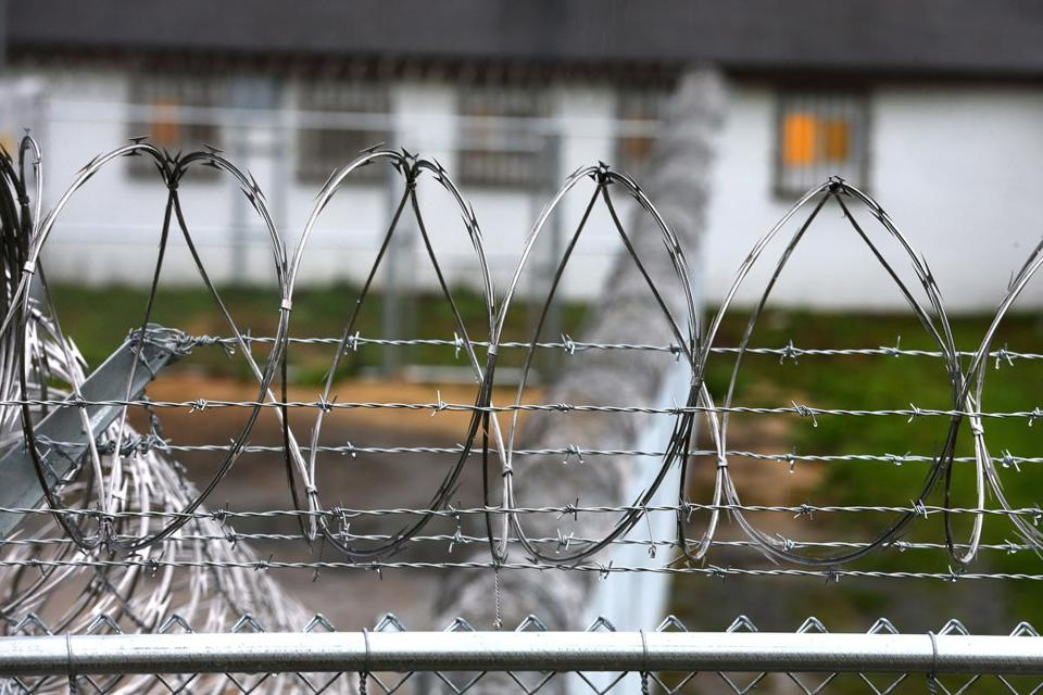 The Plymouth facility is surrounded by a tall fence and razor wire.