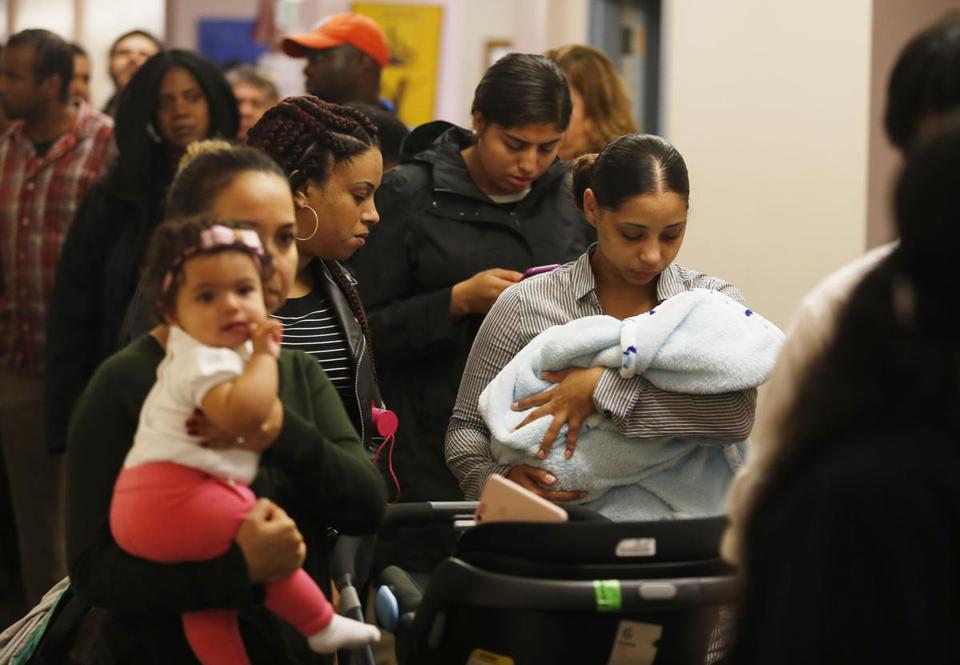 Katie De Andrade of Dorchester (right) cradled her 3- month-old son Xander De Pina as she waited for a chance to be in the lottery to live at The Beverly on Court Street.