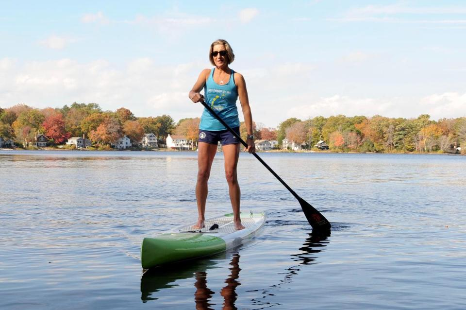 Marielle Yost, 53, who lives in Lexington and has a cottage in Magnolia, is seen paddle boarding on Chebacco Lake in Hamilton, MA Saturday, October 28, 2017. Her board is a Boga 12-6 race board with a displacement hull. (Lisa Poole for The Boston Globe)