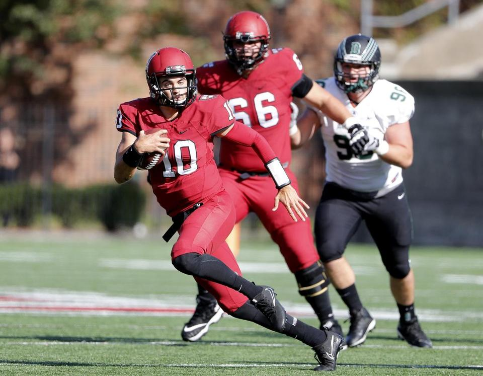 Harvard Crimson quarterback Jake Smith runs through the Dartmouth defense during their football game at Harvard Stadium in Allston, Mass., Saturday, Oct. 28, 2017. (Winslow Townson for The Boston Globe)