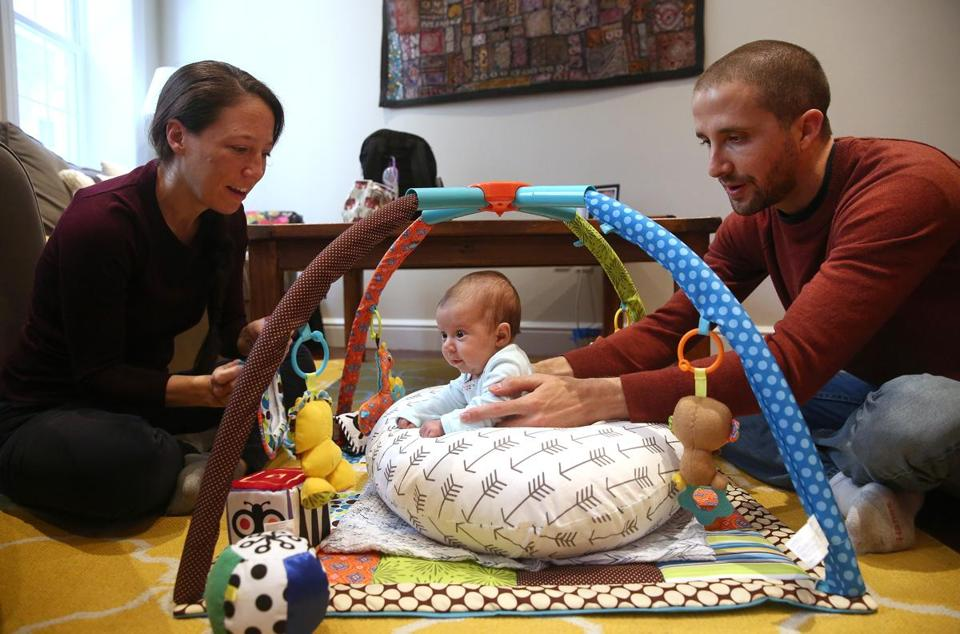 "Boston, MA - 10/17/2017 - TPTW They play ""Tummy Time"" with the activity gym. Christine and Matt Vasallo (cq) both work at Cengage Learning (cq). She's a content developer; he's an application architect. They are also both enjoying 12 weeks paid ""parental"" leave, bonding with their daughter Rosalie Vasallo (cq), who was born August 14, 2017. (Pat Greenhouse/Globe Staff) Topic: 111917parental leave Reporter: Cindy Atoji Keene"