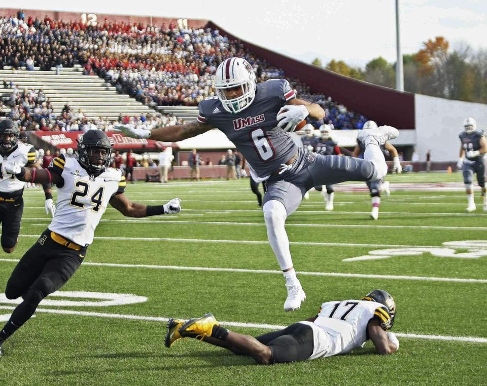 Massachusetts' Sadiq Palmer hudles over Appalachian State's Tea Hayes as Akeem Davis-Gaither, left, looks on as Palmer powers the ball in towards the end zone during the first quarter of an NCAA college football game Saturday, Oct. 28, 2017, in Amhers, Mass. (J. Anthony Roberts/The Republican via AP)
