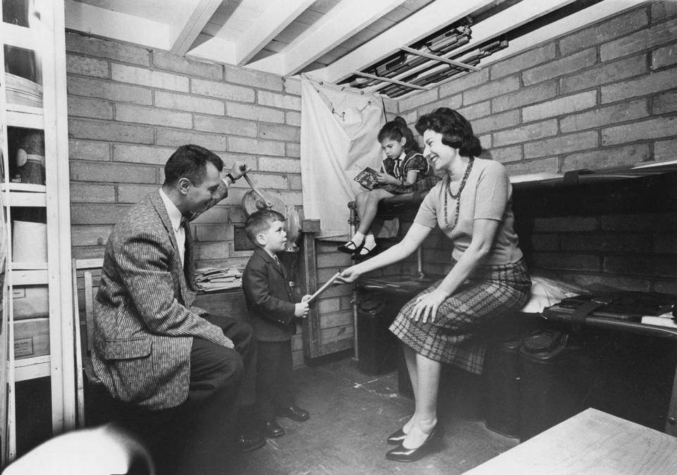 A family identified as the Bersteins of Brooklyn, in a family fallout shelter display at the New York Civil Defense headquarters, Nov. 1, 1960. Robert Blakeley's bright orange-yellow and black placards reflected Americans' anxieties about nuclear war while pointing the way to where they might be saved from it.