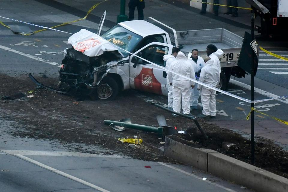 "Investigators inspect a truck following a shooting incident in New York on October 31, 2017. Several people were killed and numerous others injured in New York on Tuesday after a vehicle plowed into a pedestrian and bike path in Lower Manhattan, police said. ""The vehicle struck multiple people on the path,"" police tweeted. ""The vehicle continued south striking another vehicle. The suspect exited the vehicle displaying imitation firearms & was shot by NYPD."" / AFP PHOTO / DON EMMERTDON EMMERT/AFP/Getty Images"