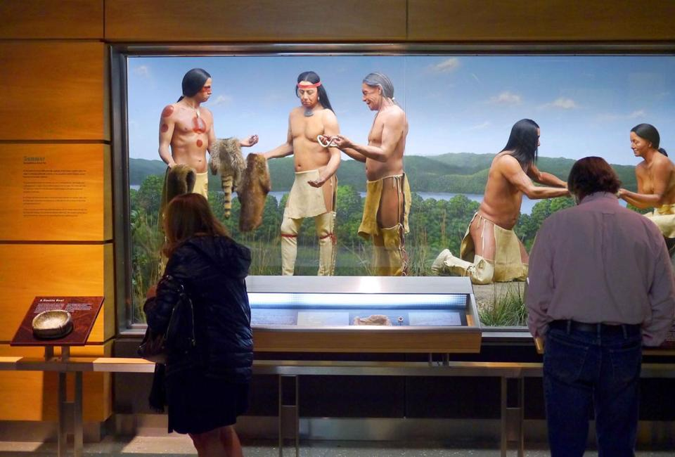 Visitors study diorama cases at the Mashantucket Pequot Museum detailing daily Pequot life.