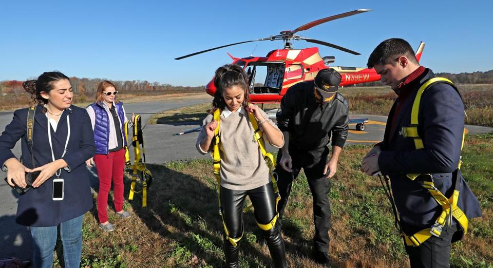 Pilot Jeff Hubbard helps prepare passengers for the Hover Boston flight at Norwood Airport.