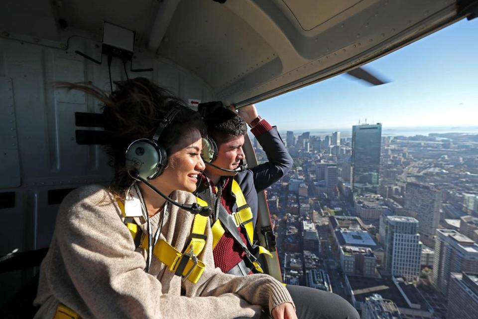 Caila Quinn and Nick Burrello in safety harnesses on their 30-minute doors-off helicopter tour of Boston.