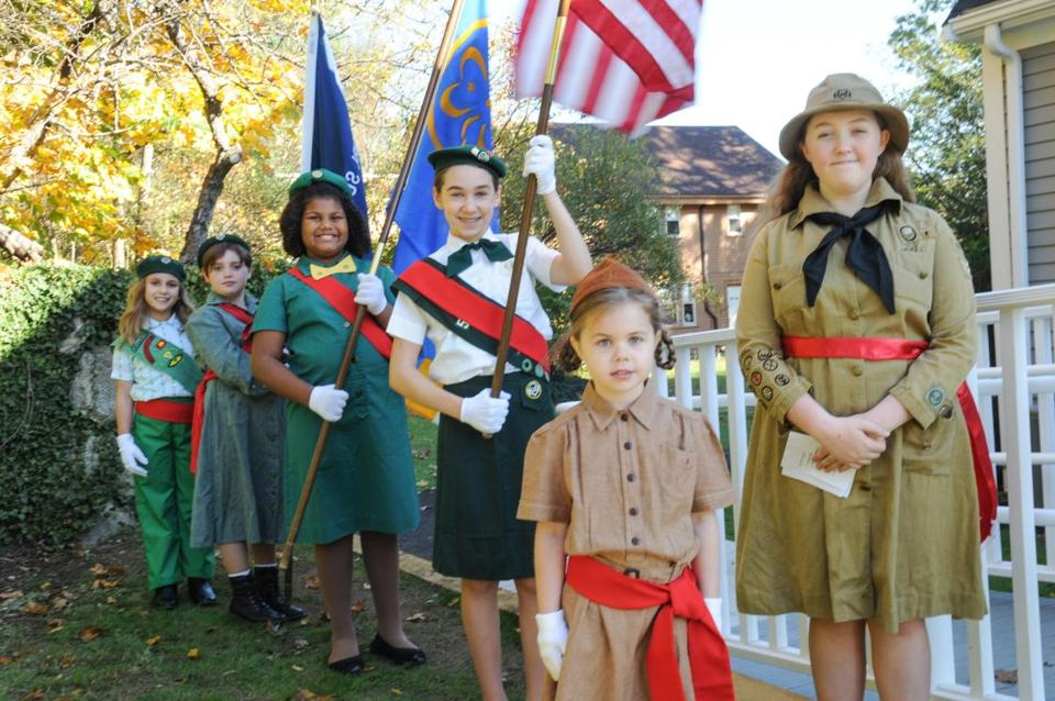 Girl Scouts in vintage uniforms (top) prepared for the flag ceremony at the Girl Scout Museum's reopening; a Scout (right) learned about old-fashioned communication; and a visitor examined archival photos and artifacts.