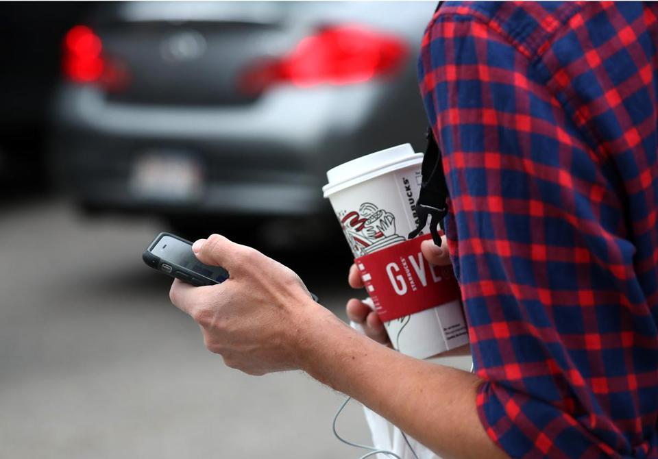 Coffee in one hand texting with another on Summer Street in morning rush hour.