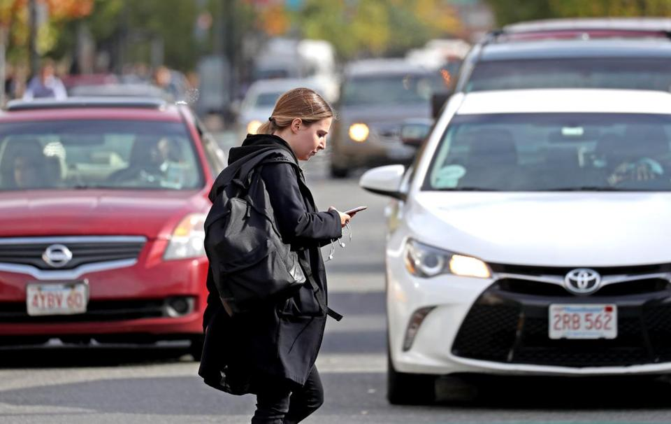 A pedestrian checked her cellphone as she walked across Commonwealth Avenue.