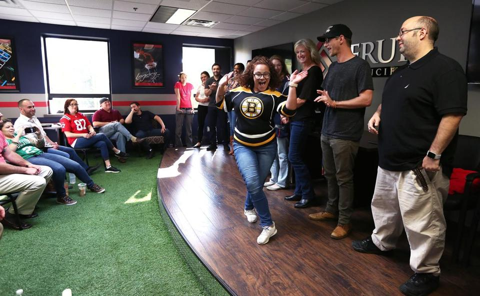 Wilmington, MA - 10/23/2017 - TPTW Delkis Aurich (cq) (Bruins shirt), and other new employees are gathered on the stage and most bust some dance moves, to glaring music, when introduced. Every Monday, Serur Agencies (cq) holds its Agency Meeting in the Turf Room. An added highlight of this recognition and motivational meeting is the presence of the company's president, David Zophin (cq), who is based in Waco, Texas. (Pat Greenhouse/Globe Staff) Topic: 111917training Reporter: XXX