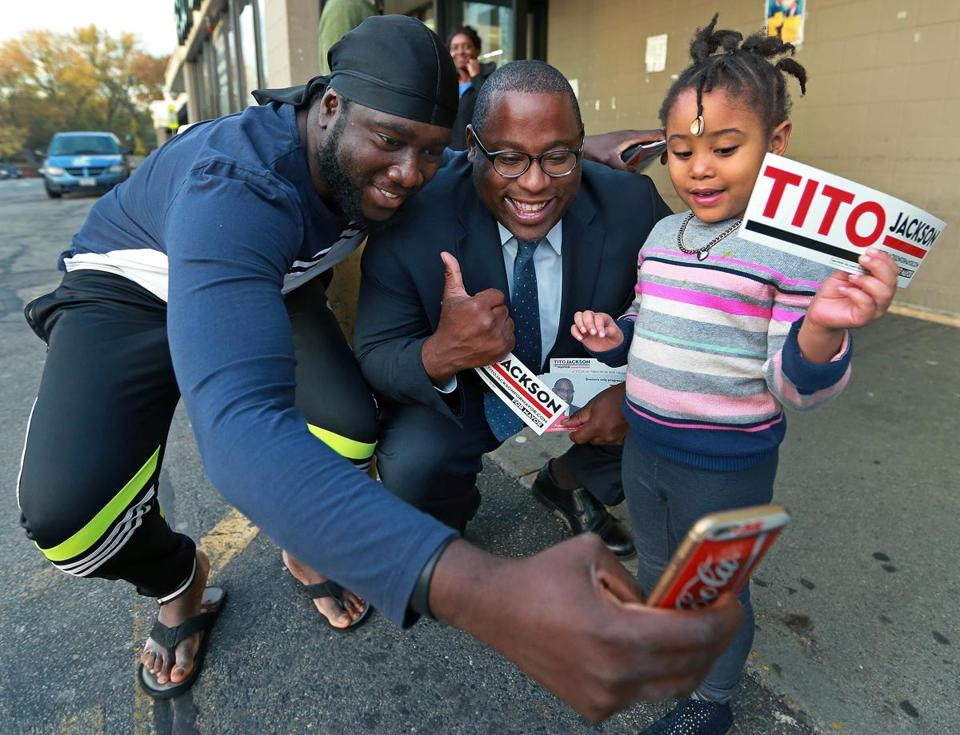 Hyde Park, MA: 11-2-17: Tito Jackson (center) is pictured as he was campaigning for mayor outside of the America's Food Basket store on Hyde Park Avenue on Thursday afternoon. He had crouched down to talk to four year old Charm Stephens (cq, right) and give her a bumper sticker when Timothy Otoo (cq, left), who was passing by on his way into the store jumped in and took a photo for himself. (Jim Davis/Globe Staff)