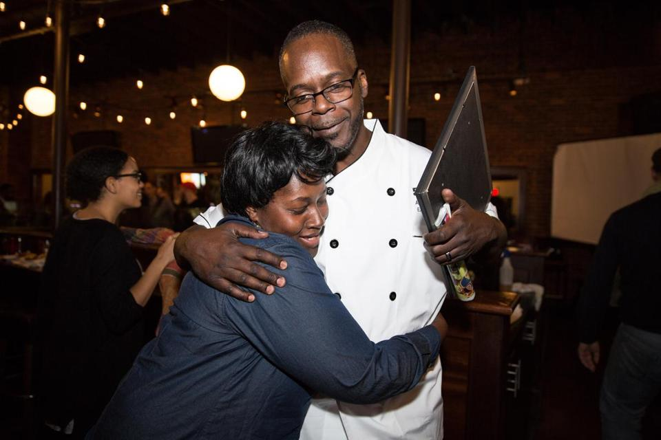 Anthony Caldwell of 50Kitchen hugged supporter Yolanda Anderson after winning the Fields Corner Collaborative's competition. Caldwell will receive free rent in a storefront on Dorchester Avenue for six months, reduced rent for a few years, and free legal and marketing coaching from other local business owners.