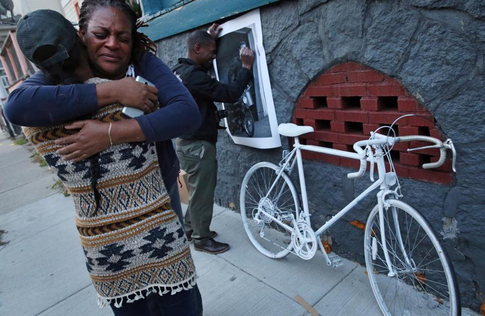 Rosemarie Davis embraced her niece Ayisha Davis during a ghost bike ceremony for Rosemarie's son Antawani Wright Davis in Dorchester on Saturday. In the background, family friend Suhayl Azan displayed a photograph he made of Antawani.