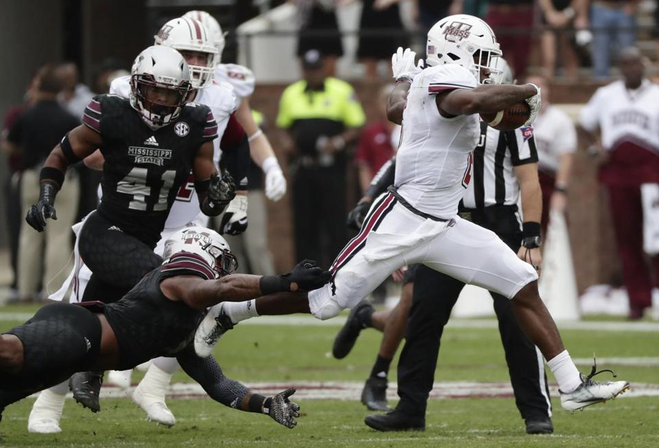 Massachusetts running back Marquis Young (8) runs through Mississippi State defenders for a first down during the first half of an NCAA college football game in Starkville, Miss., Saturday, Nov. 4, 2017. (AP Photo/Rogelio V. Solis)