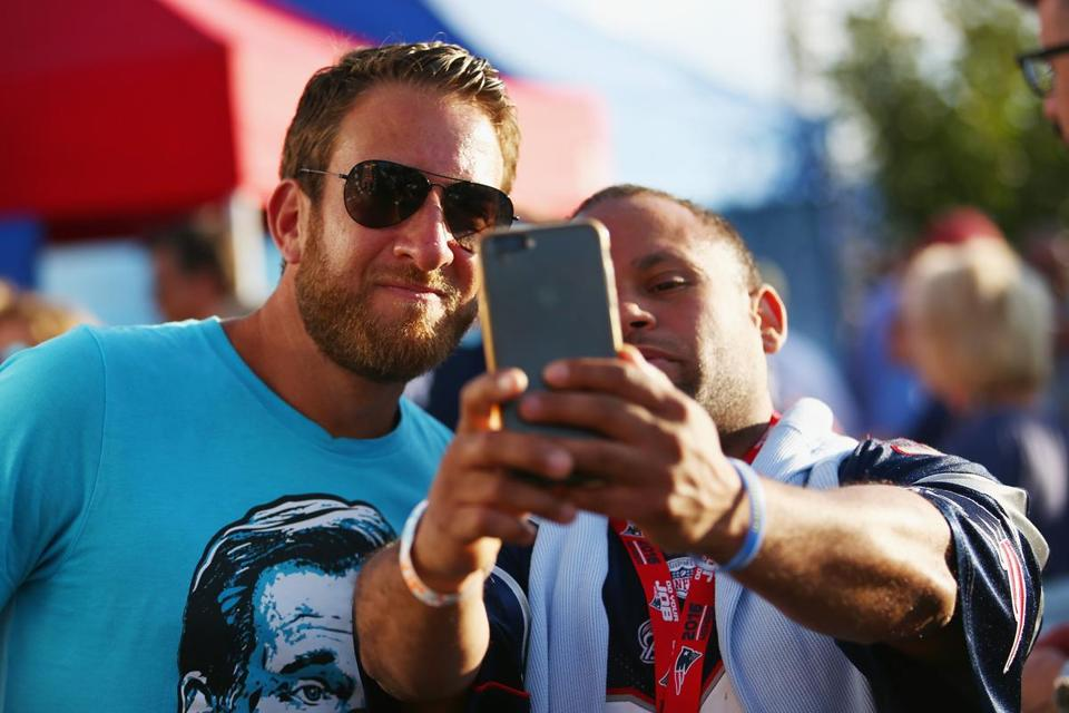 Barstool Sports founder David Portnoy (left), with a fan at a recent Patriots game in Foxborough. Barstool believes its signature brashness is a winning formula.
