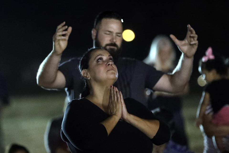 Mourners pray in a vigil for the victims of the First Baptist Church shooting Monday in Sutherland Springs, Tex.