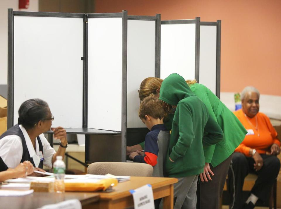 Boston, MA - 11/7/2017 - With two children, a woman votes in Ward 17, Precinct 13. Mayor Martin J. Walsh votes at the Lower Mills Branch of the Boston Public Library. He is accompanied by his partner Lorrie Higgins (cq) and her daughter Lauran/Lauren Campbell. (Pat Greenhouse/Globe Staff) Topic: 08mayoral Reporter: XXX