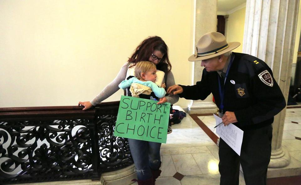 "DCR Ranger Captain Stephen Owens greeted 1-year-old Desmond Ziolo of Hopkinton. His mother, Rachael Ziolo, and others, who mostly wore green ""Support Birth Choice"" T-shirts, oppose a bill on regulating midwifery."