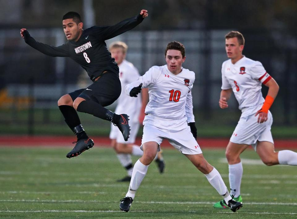 Woburn, MA: 11-8-17: Watertown's Jose Luis Mendoza (8,left) leaps by Wayland's Marco Melero (10) as he purues the ball, first half action. Watertown and Wayland met in the Division Three North Boy's Soccer semifinal match held at Woburn High School. (Jim Davis/Globe Staff)