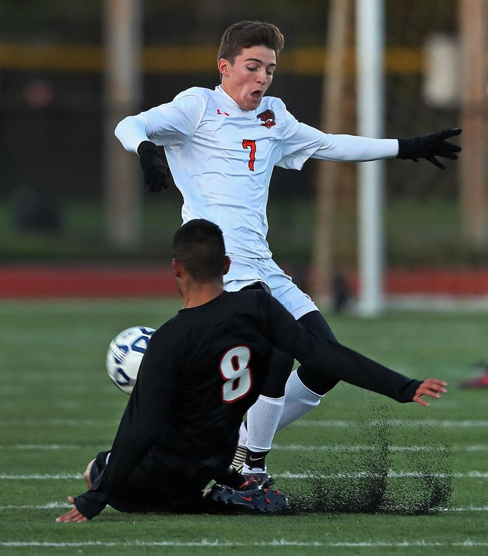 Woburn, MA: 11-8-17: Watertown's Jose Luis Mendoza (8) slides in th knock the ball away from Wayland's Andrew D'Amico (7) in first half action. Watertown and Wayland met in the Division Three North Boy's Soccer semifinal match held at Woburn High School. (Jim Davis/Globe Staff)